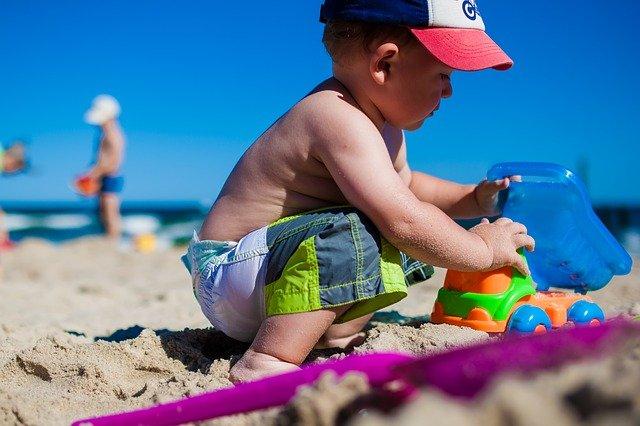 kluk s autíčkem na pláži