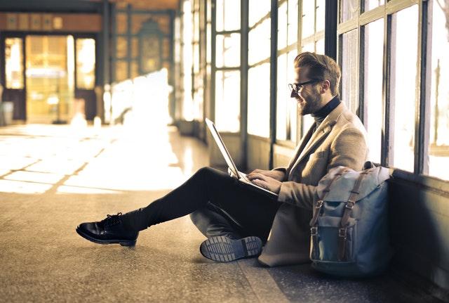 muž sedící v letištní hale na zemi vedle kufrů