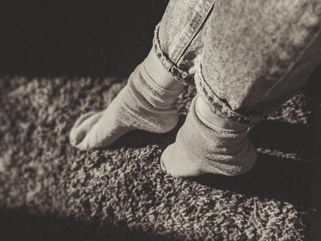nohy na koberci v šedé barvě