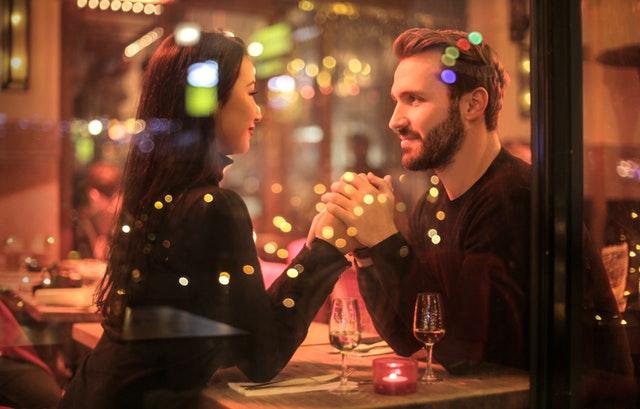 Dvojice-muž a žena sedící za oknem restaurace